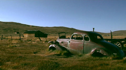 An old rusting car sits near an abandoned building in the... Stock Video Footage