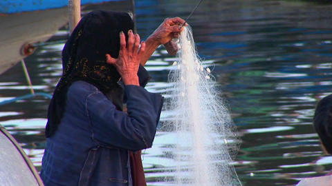 A woman works on her fishing net in Vietnam Stock Video Footage