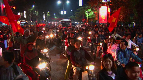 Motorcycles flying the Vietnamese flag crowd a boulevard... Stock Video Footage