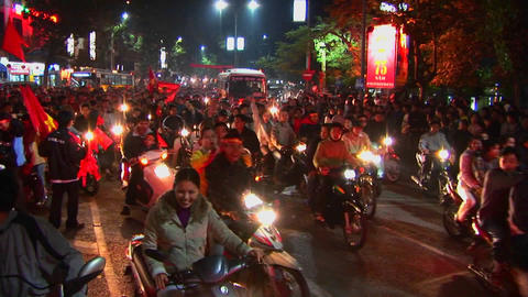 Motorcycles flying the Vietnamese flag crowd a boulevard during a political demonstration Footage