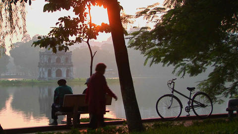 People sit in a park in Hanoi at sunset and admire the view Stock Video Footage