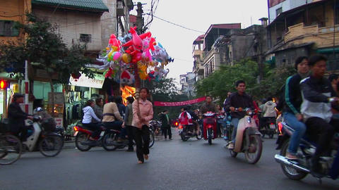 A woman walks with balloons through a busy street in... Stock Video Footage