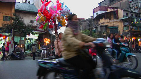 A woman walks with balloons through a busy street in Hanoi, Vietnam Footage