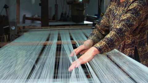 A woman works on a loom in a factory in Vietnam Footage