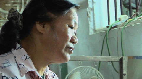 Pull back from a woman working on a loom in a factory Stock Video Footage
