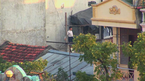 A Man Exercises On His Rooftop In The Early Morning In Vietnam stock footage