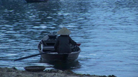 A boat is rowed across a river in Vietnam Stock Video Footage