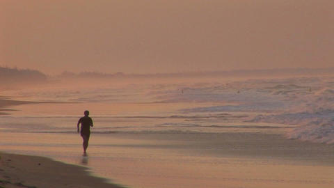 A man jogs along a beach in silhouette Footage
