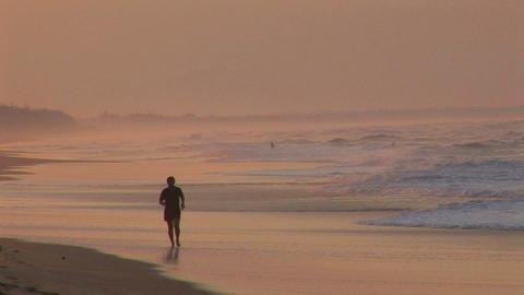 A man jogs along a beach in silhouette Stock Video Footage