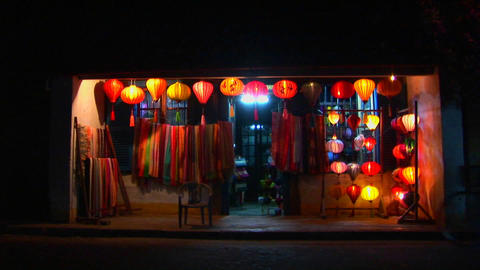 Bicycles and rickshaws pass a colorful lantern store at... Stock Video Footage