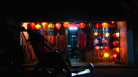 Bicycles and rickshaws pass a colorful lantern store at night in Vietnam Footage