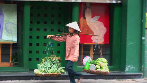A woman carries a heavy load along the street in Vietnam Stock Video Footage