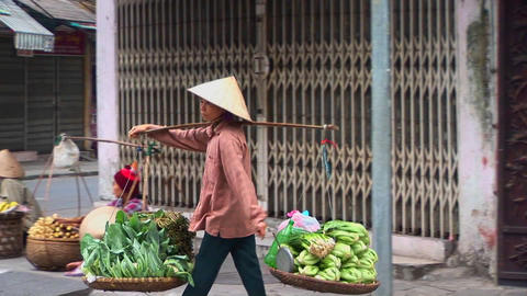 A woman carries a heavy load along the street in Vietnam Footage