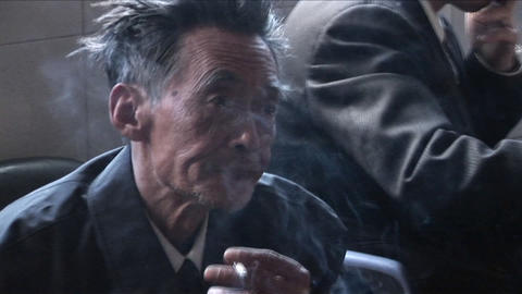 An old Chinese man smokes a cigarette and peers at the... Stock Video Footage