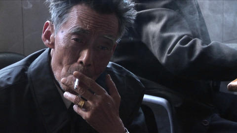 An Old Chinese Man Smokes A Cigarette And Peers At The Camera stock footage