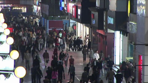 A tilt up of a nighttime mall with many pedestrians in Beijing China Footage