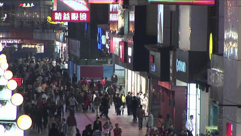 A tilt up of a nighttime mall with many pedestrians in... Stock Video Footage