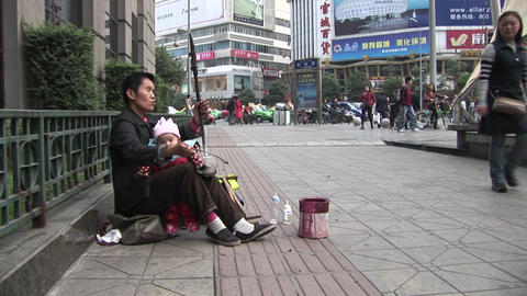 A blind man plays music along a street in modern China Footage