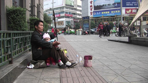 A blind man plays music along a street in modern China Stock Video Footage