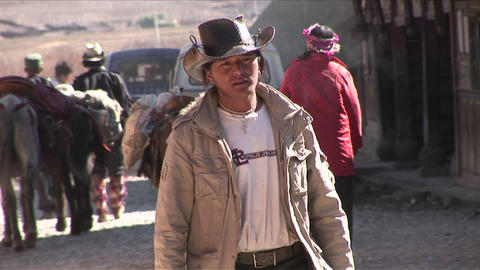 A Chinese cowboy walks through a rural village Stock Video Footage