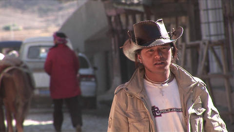 A Chinese cowboy walks through a rural village Stock Video Footage