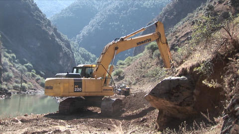 A steam shovel moves earth along a rural road Stock Video Footage