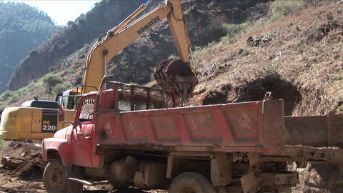 A steam shovel moves earth into a dump truck along a rural road Live Action