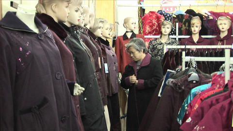 A woman shops in a clothing store with many mannequins Footage