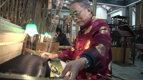 Chinese workers weave on a hand loom with great speed and accuracy Footage