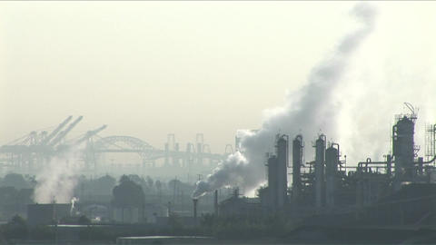 Smoke rises from a petrochemical factory or oil refinery under a cloudy sky Footage