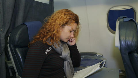 Young woman reading a magazine in an airplane flying Footage