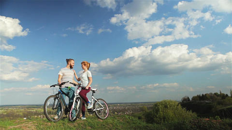 Man and woman with bicycles GIF