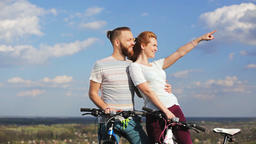Man and woman with bicycles on a hill watching the sunset Footage