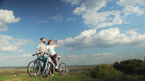 Loving couple on bicycles standing on a high hill Footage