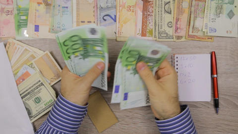 Banker counting Euros at his office table, World currencies around him Footage