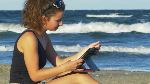 Beautiful young woman in romantic mood holding a tablet pc by the sea Footage