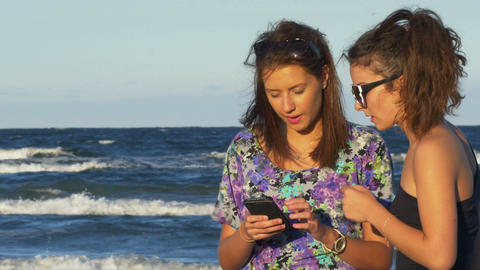 Euphoric female friends chatting and looking on a smartphone by the sea Footage