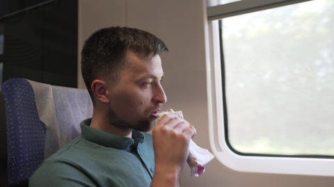 Caucasian male traveler travels in a passenger high-speed train at the window Live Action
