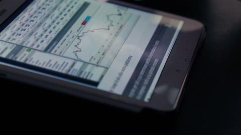 woman hand using finger for touching tablet computer pc touch screen on financial chart for business Live Action