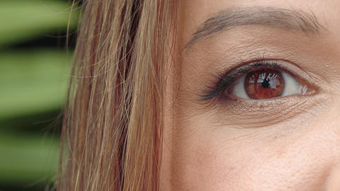 Brown woman's eye close up. The woman's eye slowly closes and opens. Perfect Live Action