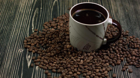 coffee cup and beans, cinnamon sticks, nuts and chocolate on wooden table on bro Footage