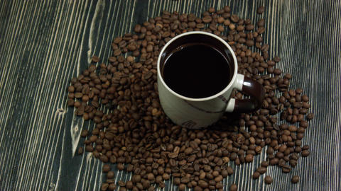 Drop falling into a cup of coffee. On a wooden background Footage