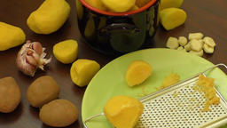Peeled new potatoes in bowl on wooden table Footage