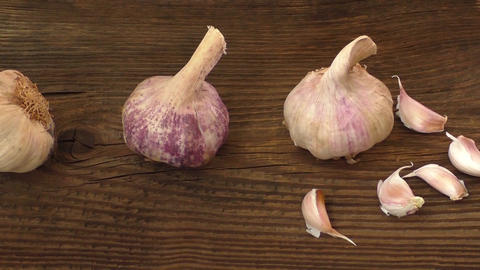 Group of single garlic cloves and a clump of garlic on wooden background Footage