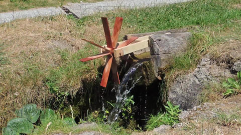 Wooden water mill kinetic toy on mountain creek. The propeller wheel is spinning Footage