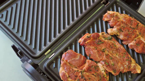 Pork neck steak marinated in herbal marinade with seasoning and grilled on elect Live Action