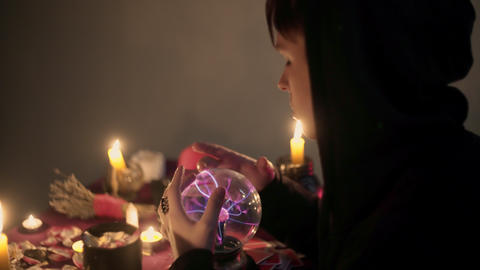 Male fortune teller performing ritual with crystal ball foreseeing future Live Action