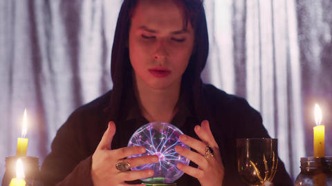 Close up of male fortune teller performing ritual with crystal ball foreseeing Live Action