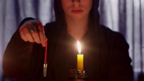 Close up of man wizard rotating a magic pendulum over a candle Live Action