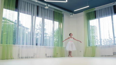 Graceful girl in skirt dances classical ballet in studio Live Action